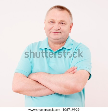 Happy middle aged man in shirt with crossed arms on his chest over white background