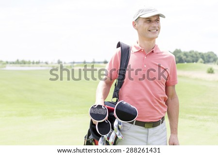 Happy middle-aged man looking away while carrying golf bag - stock photo