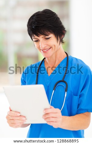 happy middle aged medical worker using tablet computer in office
