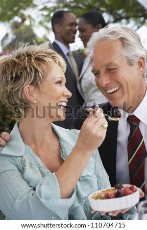 Happy middle aged woman feeding fruit salad to man - stock photo