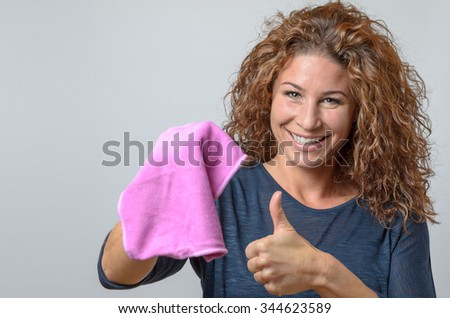 happy middle aged Woman Holding a cleaning rag and Showing Thumb Up gesture