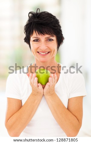 happy middle aged woman holding a green apple with both hands