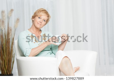 Happy middle aged woman relaxing on the couch enjoying a cup of coffee