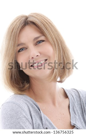 Happy middle-aged woman smiling and looking at the camera, head and shoulders studio portrait on white - stock photo