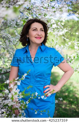 happy middle aged woman walking in blooming summer garden