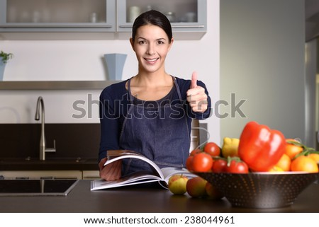 Happy middle-aged Woman Wearing Apron Standing at the Kitchen counter with Recipe Book, giving a positive thumbs up - stock photo