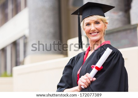 happy middle aged woman with graduation cap and gown holding diploma  - stock photo