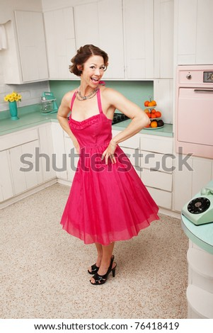 Happy middle-aged woman with hands on hips in retro-styled kitchen scene