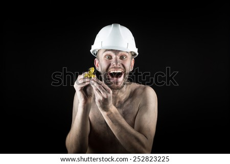 happy  miner shows a golden nugget  - stock photo