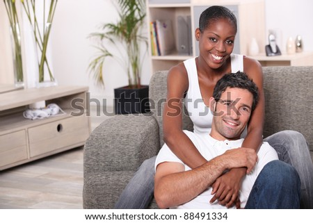 happy mixed couple at home - stock photo