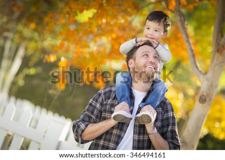 Happy Mixed Race Boy Riding Piggyback on Shoulders of Caucasian Father. - stock photo