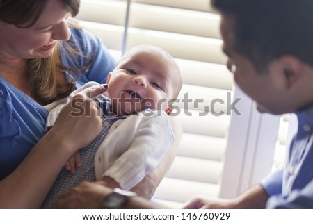 Happy Mixed Race Couple Enjoying Their Newborn Son In The Light of The Window. - stock photo