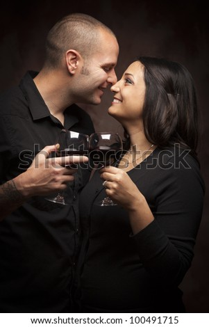 Happy Mixed Race Couple Flirting and Holding Wine Glasses on a Dark Background. - stock photo