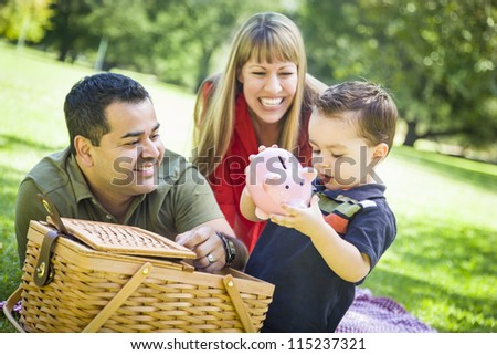 Happy Mixed Race Couple Give Their Son a Piggy Bank at a Picnic in the Park. - stock photo