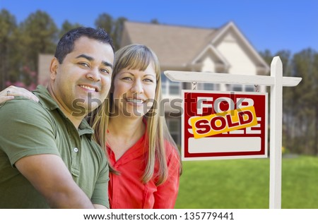 Happy Mixed Race Couple in Front of Sold Home For Sale Real Estate Sign and House. - stock photo