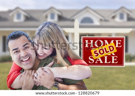 Happy Mixed Race Couple in Front of Sold Real Estate Sign and New House. - stock photo
