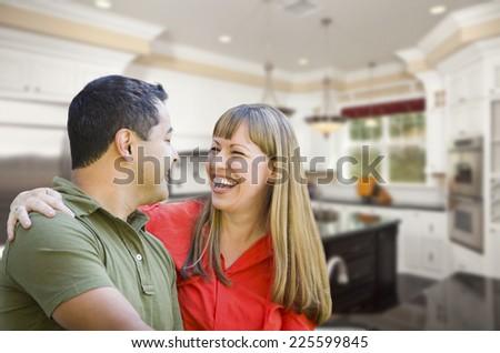 Happy Mixed Race Couple Inside Beautiful Custom Kitchen. - stock photo