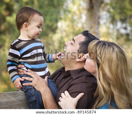 Happy Mixed Race Ethnic Family Having Fun Playing In The Park. - stock photo