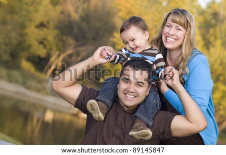Happy Mixed Race Ethnic Family Posing for A Portrait in the Park. - stock photo
