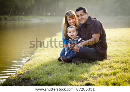 Happy Mixed Race Ethnic Family Posing for A Portrait in the Park by the Lake. - stock photo