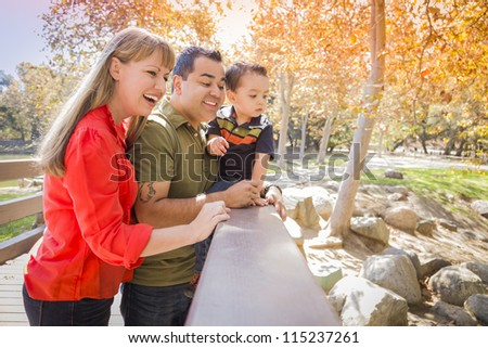 Happy Mixed Race Family Enjoy a Day at The Park Together. - stock photo