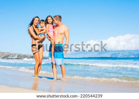 Happy Mixed Race Family of Four on Sunny Beach. Tropical Beach Vacation - stock photo