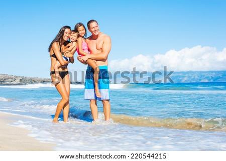 Happy Mixed Race Family of Four on Tropical Sunny Beach - stock photo
