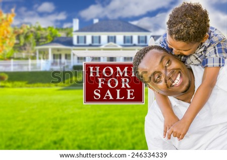 Happy Mixed Race Father and Son In Front of For Sale Real Estate Sign and New House.