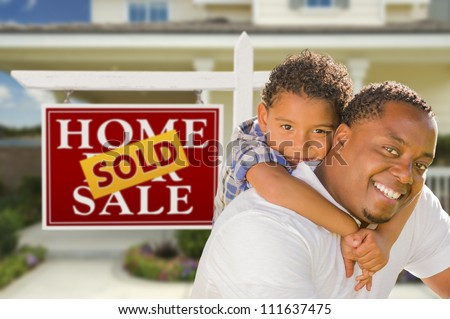 Happy Mixed Race Father and Son In Front of Sold Real Estate Sign and New House. - stock photo