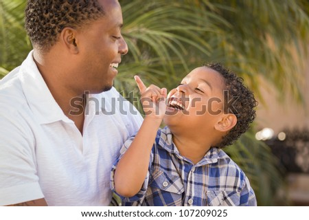 Happy Mixed Race Father and Son Playing in the Park. - stock photo