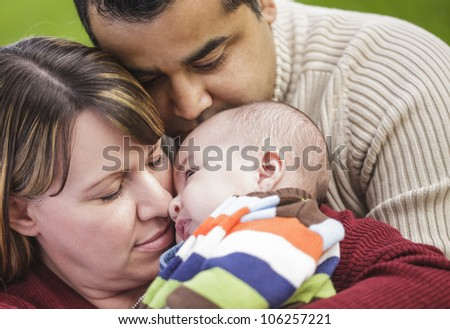 Happy Mixed Race Parents Hugging Their Son in the Park. - stock photo