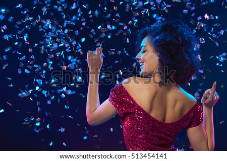 Happy mixed race woman in sequined dress dancing on a party over colorful background with confetti