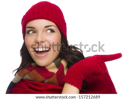 Happy Mixed Race Woman Looks and Points to the Side Wearing Winter Hat and Gloves Isolated on White Background.