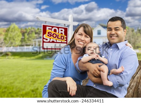Happy Mixed Race Young Family in Front of Sold Home For Sale Real Estate Sign and House. - stock photo