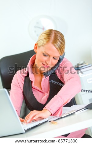 Happy modern business woman working on laptop and speaking phone - stock photo