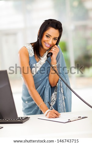 happy modern indian secretary taking message in office - stock photo