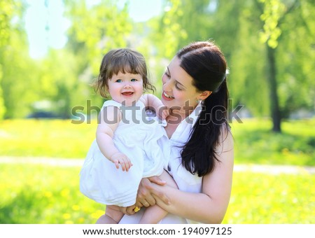 Happy mom and baby in the park in the summer, having fun, sunny day