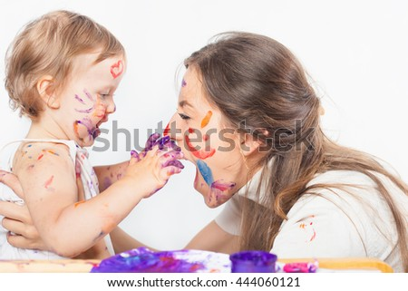 Happy mom and baby playing with painted face by paint. Games with child affect early development. Important to spend enough time with your kids.