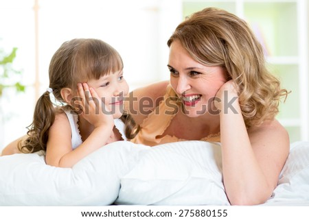 happy mom and child daughter lying on bed and looking each at other - stock photo