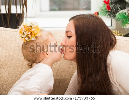 Happy mom and child girl hugging and kissing at home. The concept of cheerful childhood and family. Beautiful Mother and her baby - stock photo