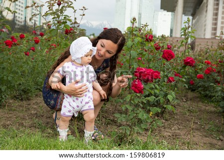 Happy mom and child girl hugging in flowers. The concept of childhood and family. Beautiful Mother and her baby outdoors - stock photo
