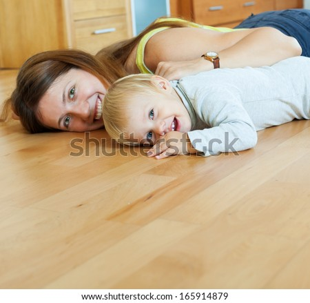 happy mom and child on wooden floor in home  - stock photo