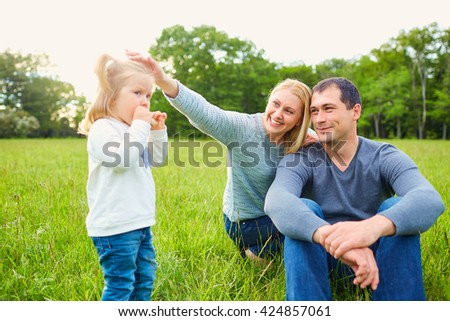 Happy mom and dads and daughter on the grass in the park. Family, smile, joy. - stock photo