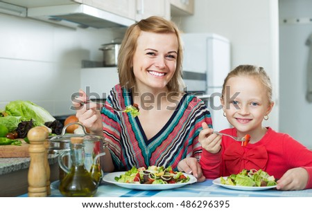 Happy mom and daughter eating vegetable salad in kitchen