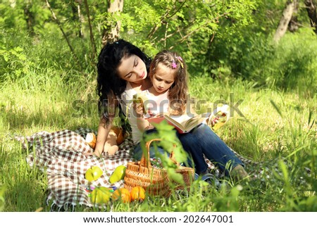 Happy mom and daughter. Picnic in the green park - stock photo
