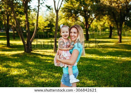 Happy mom and daughter smiling at nature.