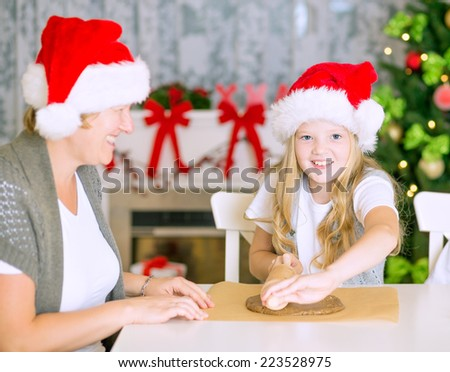 Happy mom and daughter stretching the christmas cookie dough together, baking Christmas gingerbread cookies at home, with Santa Hats, chimney and decorated Christmas Tree. - stock photo