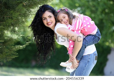 Happy mom and daughter. Walk in the green park - stock photo