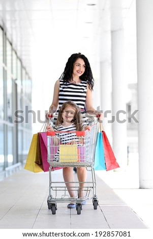 Happy mom and daughter with shop bags, outdoors - stock photo