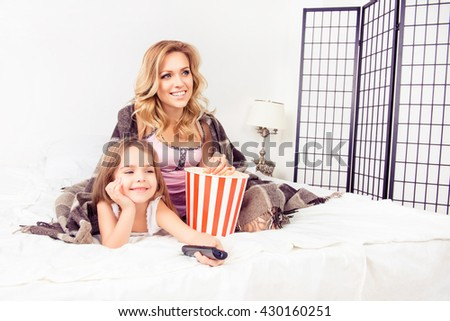 Happy mom and little daughter watching tv with popcorn
